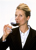 Young woman drinking red wine from stemmed glass