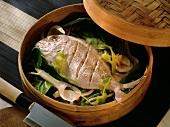 Sea bream on vegetables in steaming basket