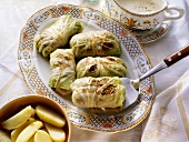 Stuffed cabbage roulade on serving dish, with potatoes
