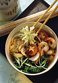 Noodle stew with shrimps, shiitake and spinach in bowl