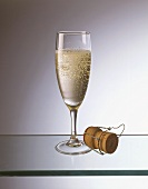 Champagne glass, with champagne cork beside it