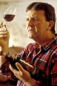 Wine grower Carlo Cataneo examining the colour of his Chianti