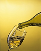 Pouring white wine from the bottle into a glass