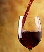 A stream of red wine flows into a red wine glass in front of a yellow background
