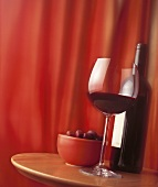 Red wine and olives on a table in front of a red curtain