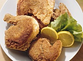 Fried chickens garnished with lettuce & lemon wedges