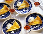 Four pieces of orange tart with cream on plates