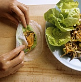 Making spring rolls: filling rice paper with vegetables