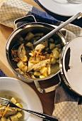 Kartoffeleintopf mit Huhn im Topf mit Kelle & auf Teller