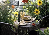 Small rattan table with two aperitifs, grissini & Parmesan