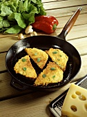 Fried, breaded Allgaeu Cheese Corners with Herbs in Cast-iron Frying Pan