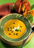 Pumpkin Cream Soup with Creme Fraiche and roasted Pumpkin Seeds in Bowl