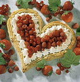 Heart-shaped cake with red berries and cream border