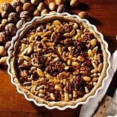 Nut tart with several types of nut in round tart tin