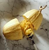 Ein Squash (Spaghettikürbis) aufgeschnitten mit Gabel