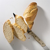 A French bread being sliced