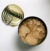 Tuna in an opened can, lid lying beside it