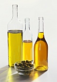 Three bottles of olive oil and green olives