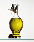 A glass bottle of olive oil and fresh olives