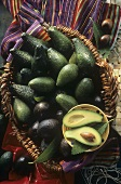 Avacados in a Basket; One Cut in Half