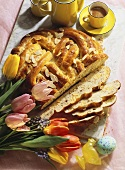 Yeast plait with almonds for Easter; tulips, coffee, Easter egg