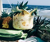 Caribbean pineapple trifle in shell on table on the beach