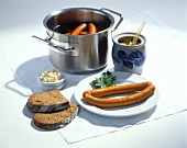 Frankfurters on a Plate and in a Pan; Mustard and Bread