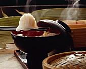 Wonton on Chopsticks Over a Bowl of Rice