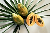 Two Whole Papayas and a Halved Papaya on Palm Leaves