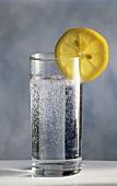 Ein Glas Mineralwasser mit Zitronenscheibe