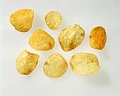 Acht einzelne Kartoffelchips vor weißem Hintergrund
