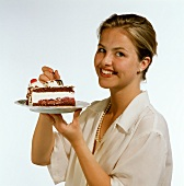 Model holding plate with piece of cherry gateau (close-up)