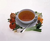 Vegetable broth in white soup cup, décor; fresh vegetables