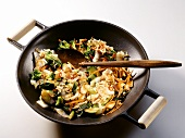 A Vegetable Stir Fry in a Wok with a Wooden Spoon