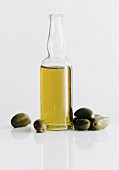 A Bottle of Olive Oil with Green Olives