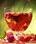 Rose punch with raspberries, limes and rose petals