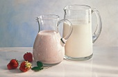 Two Glass Pitchers; One with Milk; One with Strawberry Milk