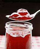 Cold-stirred strawberry jam on spoon above jar