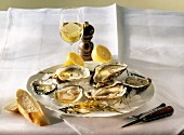 Oysters & lemon on ice on plate, wine glass on table
