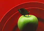 Granny Smith Apple with Leaf on Red Plate