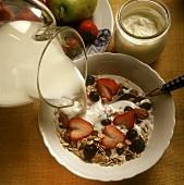 Pouring Milk Over Muesli with Berries