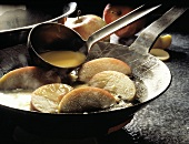 Making Apple Pancakes; Pouring Batter over Apples in a Pan