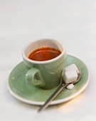 Espresso in green cup with cup and sugar cube
