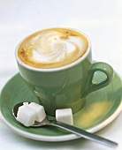 Cappuccino in green cup with spoon and sugar cubes