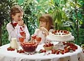 2 Mädchen am Tisch mit Erdbeerdesserts essen Erdbeercreme