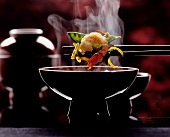 Chop Sticks Holding Steaming Shrimp and Vegetables over Bowl