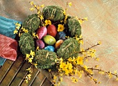 Coloured Easter eggs in Easter wreath of moss & twigs