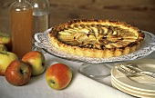 Apple tart on cake stand; apples, apple juice