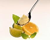 Lemon mayonnaise on spoon, decoration: lemon, limes, mint