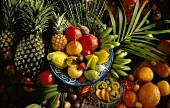 Viele tropische Früchte in Schalen & auf Tisch verteilt